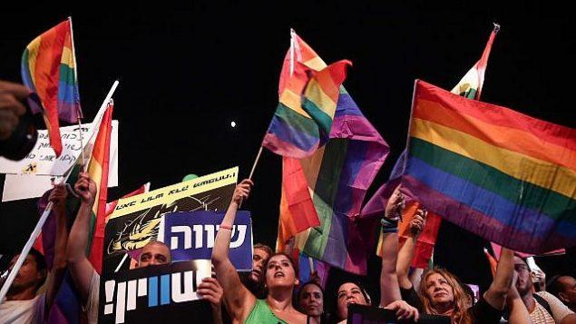 أفراد من المجتمع المثلي ومن مناصريه يشاركون في تظاهرة ضد مشروع تعديل قانون في الكنيست يحرم الأزواج المثلية من حقوق تأجير الأرحام، في ميدان 'رابين' في تل أبيب، 22 يوليو، 2018. (Miriam Alster/Flash90)