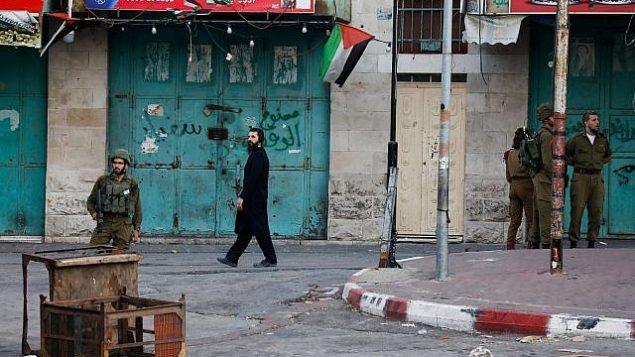 جنود يحرسون رجل أرثوذكسي متطرف يسير في مدينة الخليل بالضفة الغربية في 22 تموز / يوليو 2018. (Wisam Hashlamoun/Flash90)