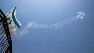 صورة لآثار الدخان في السماء التي خلفها صاروخ باتريوت تم إطلاقه لاعتراض طائرة مقاتلة سورية دخلت الأجواء الإسرائيلية من سوريا، كما شوده في مدينة صفد شمال إسرائيل، 24 يوليو، 2018.  (David Cohen/Flash90)