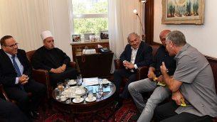 رئيس الوزراء بينيامين نتنياهو (وسط الصورة) يلتقي بالشيخ موفق طريف، الزعيم الروحي للطائفة الدرزية في إسرائيل، ووزير الاتصالات أيوب قرا (يسار الصورة) وزعماء دروز آخرين في مكتبه في القدس لمناقشة قانون 'الدولة القومية' في 27 يوليو، 2018. (Kobi Gideon/GPO/Flash90)
