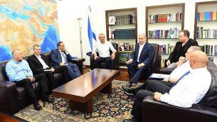 رئيس الوزراء بينيامين نتنياهو (وسط-يمين) خلال لقاء جمعه بوزير المالية موشيه كحلون (وسط-يسار) ووزير الاتصالات أيوب قرا (الثالث من اليسار) ووزير السياح ياريف ليفين (الثاني من اليسار)  وعضو الكنيست عن حزب 'كولانو' أكرم حسون (من اليسار) وعضو الكنيست عن حزب 'إسرائيل بيتنا' حمد عمار (من اليمين) ووزير الدفاع أفيغدور ليبرمان (الثاني من اليمين) وكبير موظفي نتنياهو، يوآف هوروفيتس (الثالث من اليمين) في 26 يوليو، 2018. (Haim Tzach/GPO)