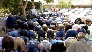 يشارك المصلين المسلمين في صلاة الظهر في موقف للسيارات بالقرب من بوابة الأسباط في مدينة القدس القديمة، رافضين الدخول إلى منطقة الحرك للوصول إلى المسجد الأقصى في الداخل، 25 يوليو 2017. (دوف ليبر / تايمز أوف إسرائيل)