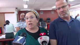 نيريت زامورا تتحدث مع صحفيين داخل محكمة يهودا العسكرية، الى جانب زوجها، قبل محاكمة منفذ هجوم ضدها، 16 يوليو 2018 (Screen capture/Israel National News)
