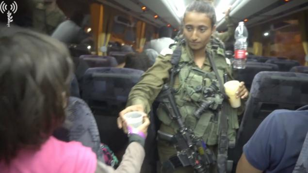 جنود إسرائيليون يوزعون الماء على عناصر 'الخوذ البيضاء' وعائلاتهم، الذين قامت إسرائيل بإجلائهم من سوريا إلى الأردن،  بعد فرارهم من نظام الأسد، 22 يوليو، 2018.  (الجيش الإسرائيلي)