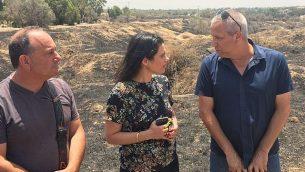 وزيرة العدل إيليت شاكيد (وسط) تقابل سكان المجتمعات الإسرائيلية بالقرب من قطاع غزة في 3 يوليو 2018، في حقل أحرقته البالونات الحارقة والطائرات الورقية. (Courtesy)