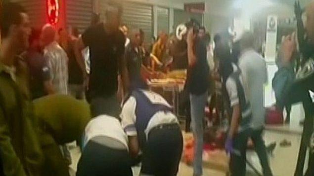 مسعفون يعالجون الضحايا بعد هجوم في محطة بئر السبع المركزية للحافلات في 18 أكتوبر 2015. (screen capture: Channel 2)