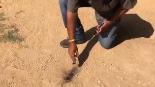 رجل يتفقد موقع سقوط بالون في ساحة روضة أطفال في المجلس الإقليمي سدون خنيغف في 17 يوليو، 2018.  (لقطة شاشة: القناة 10)