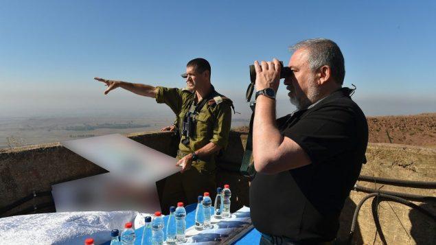 وزير الدفاع افيغادور ليبرمان ينظر الى الحدود مع سوريا بينما يبلغه الجنرال عميت فيشر باخر التطورات في جنب سوريا، 10 يوليو 2018 (Ariel Hermoni/Defense Ministry)