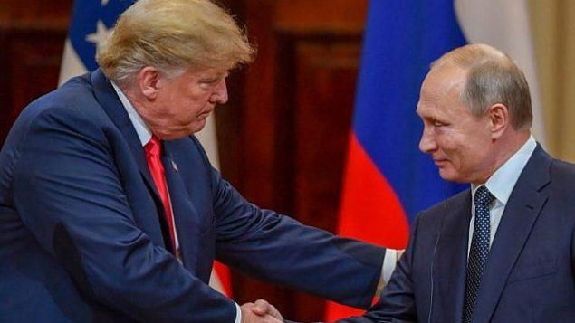 الرئيس الأمريكي دونالد ترامب (من اليسار) ونظيره الروسي فلاديمير بوتين يتصافحان قبيل عقد مؤتمر صحفي مشترك بعد لقائهما في القصر الرئاسي في هلسنكي، 16 يوليو، 2018.  (AFP PHOTO/ Yuri KADOBNOV)