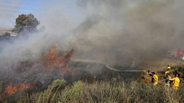 رجال إطفاء يعملون على إخماد حريق قرب مدينة سديروت الجنوبية ناجم عن بالون حارق أُطلق من قطاع غزة في 31 يوليو 2018. (AFP Photo/Menahem Kahana)