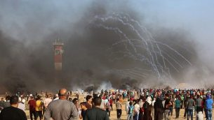 إطلاق قنابل الغاز المسيل للدموع من قبل القوات الإسرائيلية خلال مظاهرة على الحدود بين إسرائيل وقطاع غزة على متظاهرون فلسطينيون، في خان يونس جنوب قطاع غزة في 3 أغسطس / آب 2018. (AFP/Said Khatib)