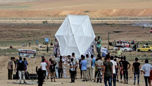 فلسطينيون يستعدون لإطلاق طائرة ورقية بالقرب من الحدود بين غزة وإسرائيل، شرقي جباليا، 3 أغسطس، 2018.  (AFP/ MAHMUD HAMS)