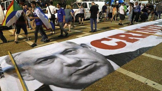 لافتة سياسية مع صورة رئيس الوزراء بنيامين نتنياهو على الارض خلال مظاهرة للدروز الإسرائيليين وداعميهم ضد قانون الدولة اليهودية في تل ابيب، 4 اغسطس 2018 (AFP PHOTO / JACK GUEZ)