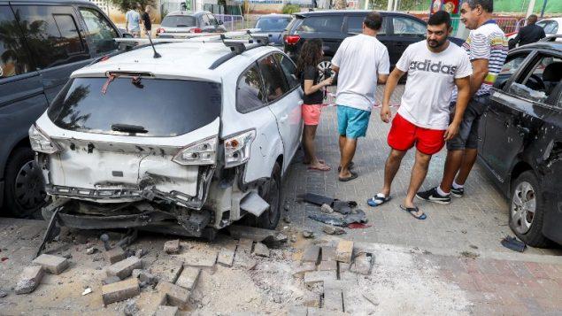 رجال اسرائيليون يقفون بجانب سيارة تضررت نتيجة قوط صاروخ اطلق من قطاع غزة في بلدة سديروت الإسرايلية في جنوب اسرائيل، 9 اغسطس 2018 (AFP PHOTO / JACK GUEZ)