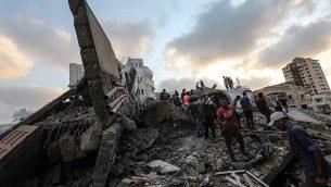 صورة تم التقاطها في 9 أغسطس، 2018 تظهر أشخاصا يتفقدون أنقاض مركز ثقافي في أعقاب غارة جوية إسرائيلية على مدينة غزة. (AFP PHOTO / MAHMUD HAMS)