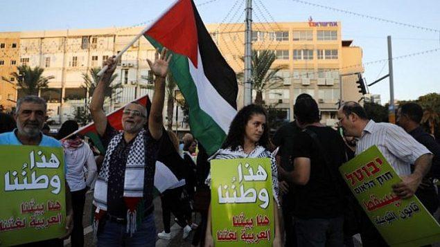 متظاهرون يحملون لافتات خلال مظاهرة ضد قانون الدولة اليهودية في تل أبيب، 11 اغسطس 2018 (AFP/Ahmad GHARABLI)
