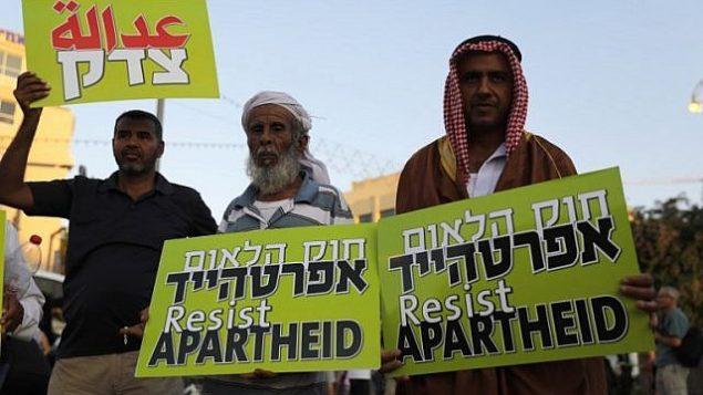مواطنون إسرائيليون عرب يحملون لافتات خلال مظاهرة احتجاجية على قانون الدولة القومية في تل أبيب، 11 أغسطس، 2018.  (AFP/ Ahmad GHARABLI)