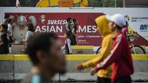 يمارس الناس الرياضة بالقرب من لافتة الألعاب الآسيوية لعام 2018 خلال يوم خالٍ من السيارات في جاكرتا في 12 أغسطس، 2018. (وكالة الصحافة الفرنسية (AFP PHOTO / BAY ISMOYO)