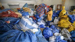 موظف في مكتب البريد الفلسطيني يدقق في أكياس بريد لم يتم تسليمها يعود تاريخها إلى عام 2010، بعد أن منعت إسرائيل إدخالها، في مكتب التبادل البريدي الدولي في مدينة أريحا في الضفة الغربية، 14 أغسطس، 2018.  (AFP / ABBAS MOMANI)