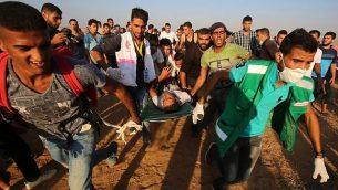 مسعفون فلسطينيون يحملون متظاهر مصاب خلال التظاهرات على الحدود بين إسرائيل وقطاع غزة، شرق خان يونس في جنوب قطاع غزة في 24 أغسطس / آب 2018. (AFP/Said Khatib)