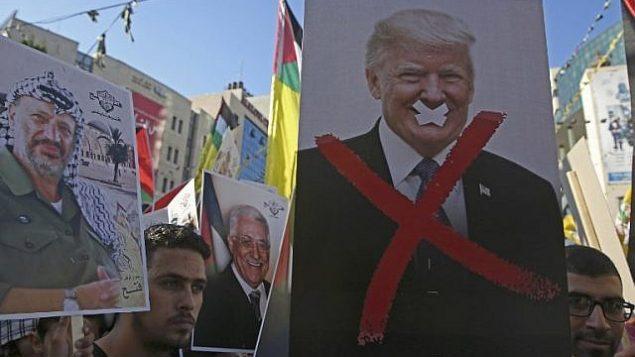 في هذه الصورة من 17 يوليو، 2018، يحمل متظاهرون فلسطينيون صورا للزعيم الفلسطيني الراحل ياسر عرفات والرئيس الأمريكي دونالد ترامب خلال مسيرة لدعم حركة 'فتح' في مدينة نابلس في الضفة الغربية. (AFP Photo/Jaafar Ashtiyeh)