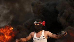محتج فلسطيني ملثِّم يحمل مقلاعا ويقف أمام الدخان المتصاعد من الإطارات المحترقة خلال احتجاج بالقرب من الحدود مع إسرائيل شرق مدينة غزة في 31 آب / أغسطس، 2018. (AFP PHOTO / MAHMUD HAMS)