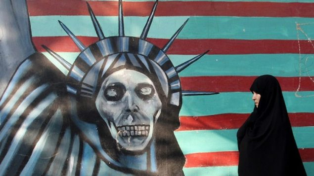 امرأة إيرانية تسير بجانب لوحة جدارية على جدار السفارة الأمريكية السابقة في العاصمة الإيرانية طهران، 9 نوفمبر / تشرين الثاني 2016. (AFP/Atta Kenare)