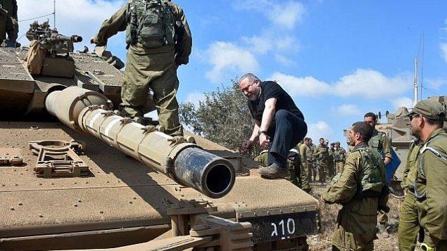 وزير الدفاع أفيغدور ليبرمان يتسلق دبابة في مرتفعات الجولان في 7 أغسطس عام 2018. (Ariel Hermoni/Defense Ministry)