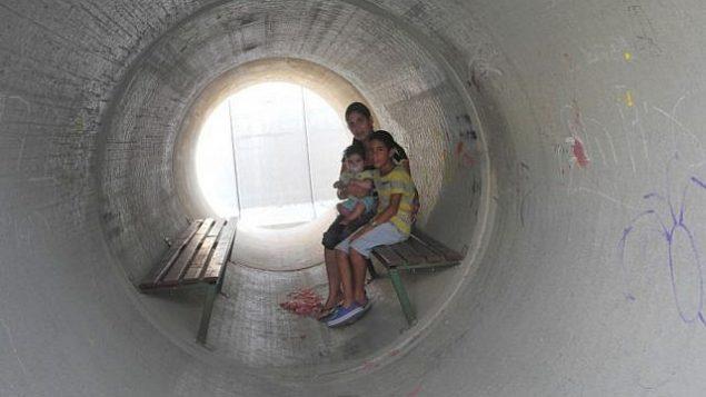 توضيحية: عائلة إسرائيلية تختبئ في ملجأ مصنوع من أنبوب إسمنتي خلال حرب غزة 2014.  (Melanie Lidman/Times of Israel)