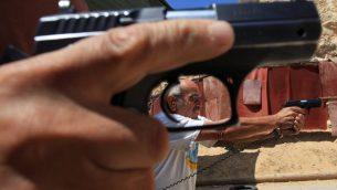 صورة توضيحية: رجل يحمل مسدس (Nati Shohat/Flash90)