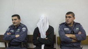 بن درعي، وسط الصورة، شرطي حرس الحدود المتهم بإطلاق النار على شاب فلسطيني وقتله في مواجهات في بيتونيا في الضفة الغربية، خلال جلسة في المحكمة المركزية في القدس، 30 ديسمبر، 2014. (Yonatan Sindel/Flash90)