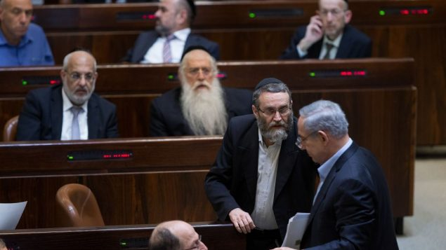 عضو الكنيست من حزب 'يهدوت هتوراة' موشيه غافني يتحدث مع رئيس الوزراء بنيامين نتنياهو في الكنيست، 24 نوفمبر 2015 (Yonatan Sindel/Flash90)