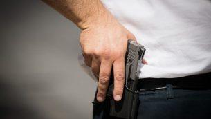 صورة توضيحية: رجل يحمل مسدس (Yonatan Sindel/Flash90)