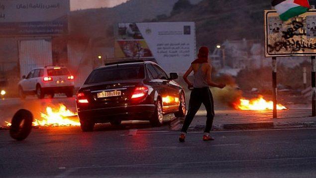 توضيحية: مواجهات بين متظاهرين فلسطينيين والقوات الإسرائيلية خلال مظاهرات بالقرب من حاجز حوارة، جنوب مدينة نابلس في الضفة الغربية، 14 مايو، 2018. (Nasser Ishtayeh/Flash90)