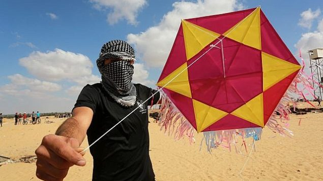محتج فلسطيني يقوم بإطلاق طائرة ورقية محملة بمواد حارقة باتجاه إسرائيل خلال مظاهرة على الحدود مع إسرائيل، شرقي مدينة رفح في جنوب قطاع غزة، 29 يونيو، 2018. (Abed Rahim Khatib/Flash90)