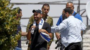 إيلور عزاريا، مركز، يزور مدينة الخليل في الضفة الغربية بعد اطلاق سراحه من السجن، حيث قضى عقوبة بتهمة القتل غير المتعمد عام 2016 لمعتدي فلسطيني في المدينة خلال خدمته العسكرية، 3 يوليو 2018 (Wisam Hashlamoun/Flash90)