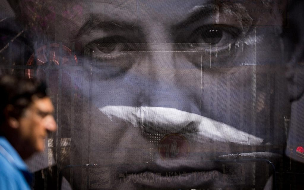 رجل بيمر من أمام ملصق ينتقد رئيس الوزراء بينيامين نتنياهو بالقرب من مقر إقامته في القدس، مع وصول المحققين للتحقيق معه في مزاعم فساد، 10 يوليو، 2018. (Yonatan Sindel/Flash90)