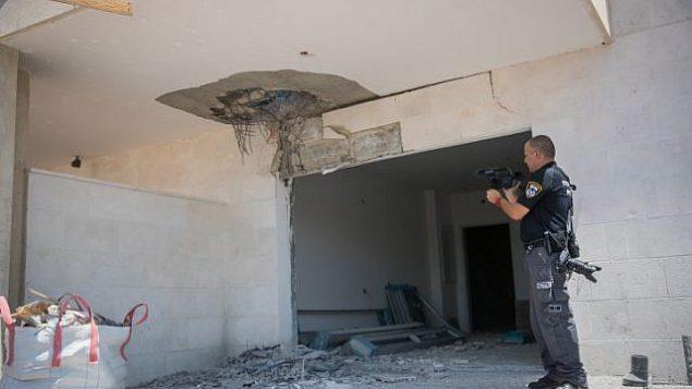 شرطي إسرائيلي يتفقد الأضرار التي لحقت لموقع بناء في  بلدة سديروت الواقعة جنوب إسرائيل بالقرب من الحدود مع غزة في أعقاب سقوط صاروخ في الموقع، 9 أغسطس، 2018.  (Yonatan Sindel/Flash90)
