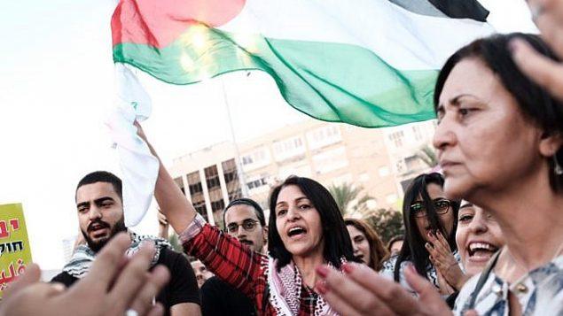 عرب اسرائيليون يرفعون اعلام فلسطينية خلال مظاهرة ضد قانون الدولة اليهودية في ساحة رابين في تل ابيب، 11 اغسطس 2018 (Tomer Neuberg/Flash90)