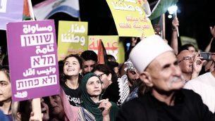مواطنون إسرائيليون عرب يتظاهرون ضد 'قانون الدولة القومية' في تل أبيب، 11 أغسطس، يرقع بعضهم الأعلام الفلسطينية. (Tomer Neuberg/Flash90)