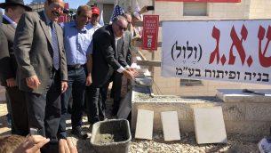 محافظ اركنساس السابق مايك هكابي يضع الحجارة في مجمع سكني جديد في مستوطنة افرات في الضفة الغربية، 1 اغسطس 2018 (Jacob Magid/Times of Israel)