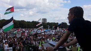 """يتحدث سيوماس ميلن إلى تظاهرة معادية لإسرائيل خلال """"الجرف الصامد"""" عام 2014. (موقع YouTube)"""