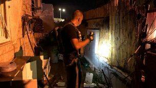 مفتش شرطة يفتش فناء منزل في بلدة سديروت بجنوب إسرائيل أصيب بهجوم صاروخي من قطاع غزة في 8 أغسطس / آب 2018. (الشرطة الإسرائيلية)