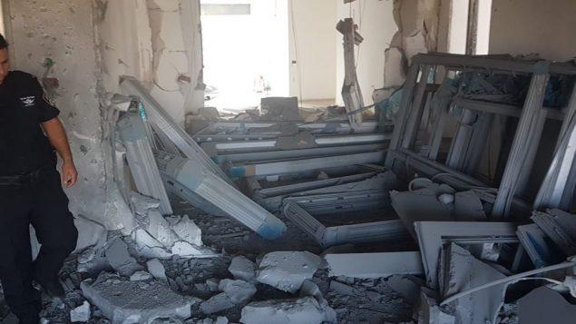 شرطي اسرائيلي يفحص اضرار في موقع بناء داخل مدينة سديروت في جنوب اسرائيل بالقرب من حدود غزة بعد سقوط صاروخ، 9 اغسطس 2018 (Israel Police)