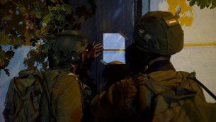 جنود إسرائيليون يعلقون إخطار هدم على منزل منفذ هجوم فلسطيني من قرية كوبر الفلسطينية في الضفة الغربية قام قتل إسرائيلي طعنا في الشهر الماضي، 13 أغسطس، 2018. (الجيش الإسرائيلي)
