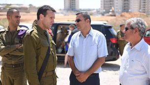 رئيس القيادة الجنوبية للجيش الإسرائيلي جنرال هرتسل هاليفي، يسار وسط، يتحدث مع رئيس بلدية سديروت ألون دافيدي، يمين وسط، خلال زيارة إلى البلدة الجنوبية، التي تعرضت مرارًا وتكرارًا لإطلاق الصواريخ من قطاع غزة في أغسطس 9، 2018. (الجيش الإسرائيلي)
