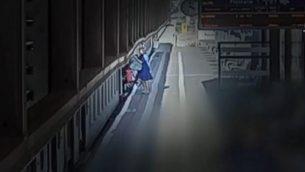 تكافح أورتال يعكوف لتحميل عربة طفلتها إلى القطار في محطة الخضيرة. (لقطة شاشة: القناة 10)