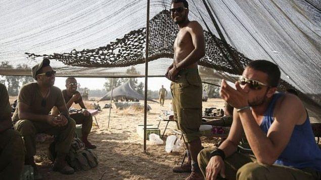 توضيحية: جنود إسرائيليون بدو في خيمة في ميدان بالقرب من حدود غزة في جنوب إسرائيل، 6 يوليو، 2014. (Hadas Parush/Flash90)