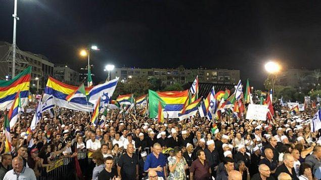 متظاهرون يلوحون بالأعلام الإسرائيلية والدرزية خلال مظاهرة في تل ابيب ضد قانون الدولة اليهودية، 4 اغسطس 2018 (Adam Rasgon/ Times of Israel staff)