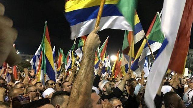 متظاهرون يلوحون بالأعلام الإسرائيلية والدرزية خلال مظاهرة في تل ابيب ضد قانون الدولة اليهودية، 4 اغسطس 2018 (Luke Tress / Times of Israel staff)